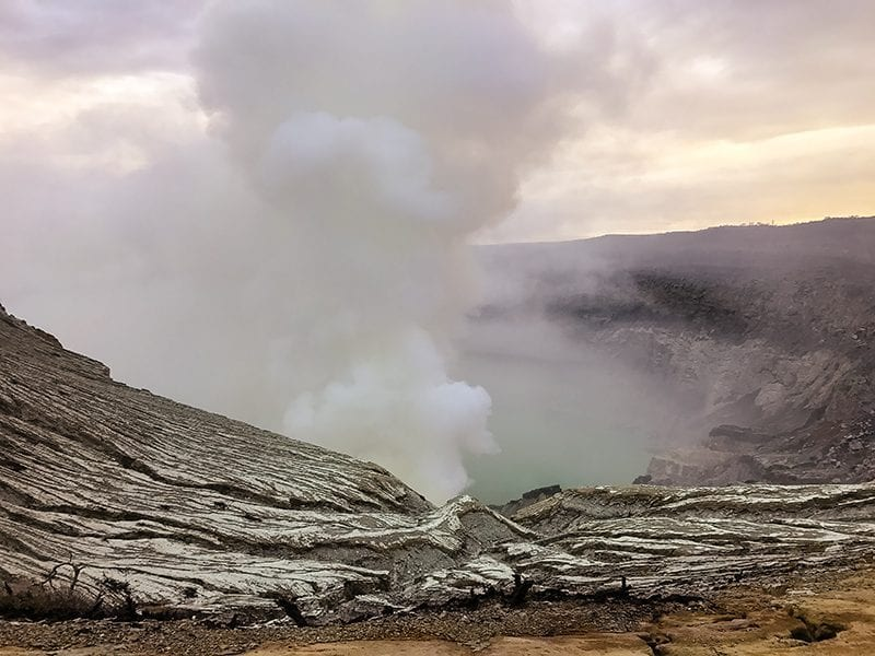 Ijen volcano crater in the daylight with steam coming out of the turquoise sulphur lake below