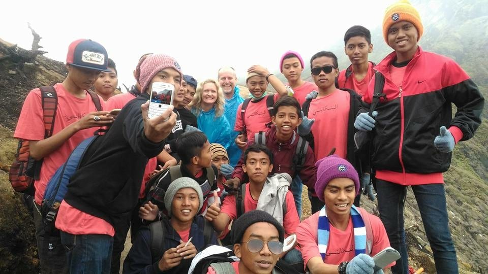 Photos of group of Indonesian travellers wearing pink and black jackets with Larch and Alan wearing blue on Ijen Volcano