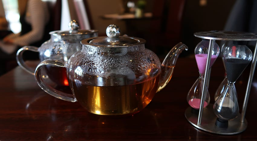 Two elegant glass teapots with brewing timer