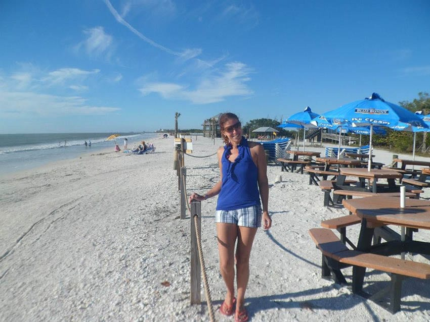 Anne from Travel Well 4 Less standing on a white sandy beach wearing white and blue striped shorts and a blue top