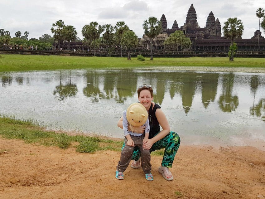 Cathy from Mummy Travels with her young daughter in front of a lake in Cambodia
