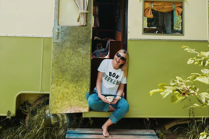 Claire from The Weekend Candy sitting cross legged in the doorway of a green and cream caravan