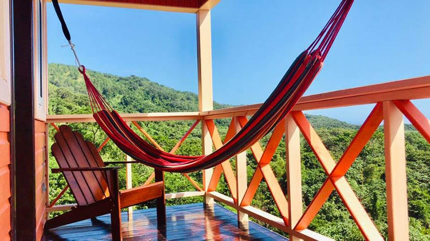 The balcony at Las Casitas de Mi Casa Too with chair and hammock overlooking the lush jungle and blue skies