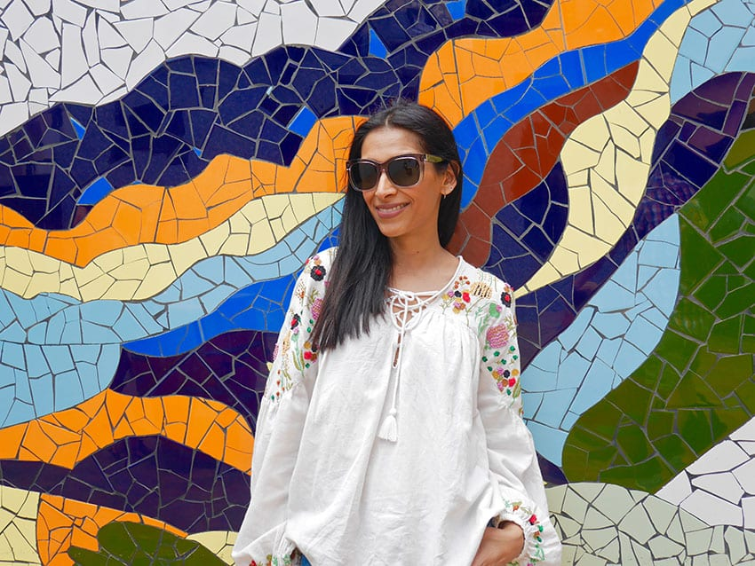 Sima from The Curious Pixie wearing a white top and sunglasses in front of a colourful mosaic wall