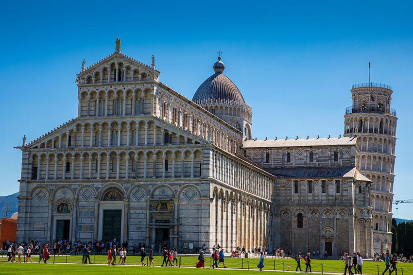 "The white Leaning Tower of Pisa behind the Duomo in the ""Piazza dei Miracoli"" in Pisa with blue skies and green grass"