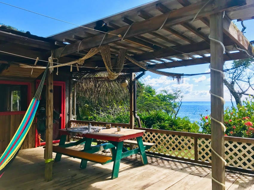 Guanaja Backpackers Hostel with views over the sea from the shaded colourful hammock and table and bench seating