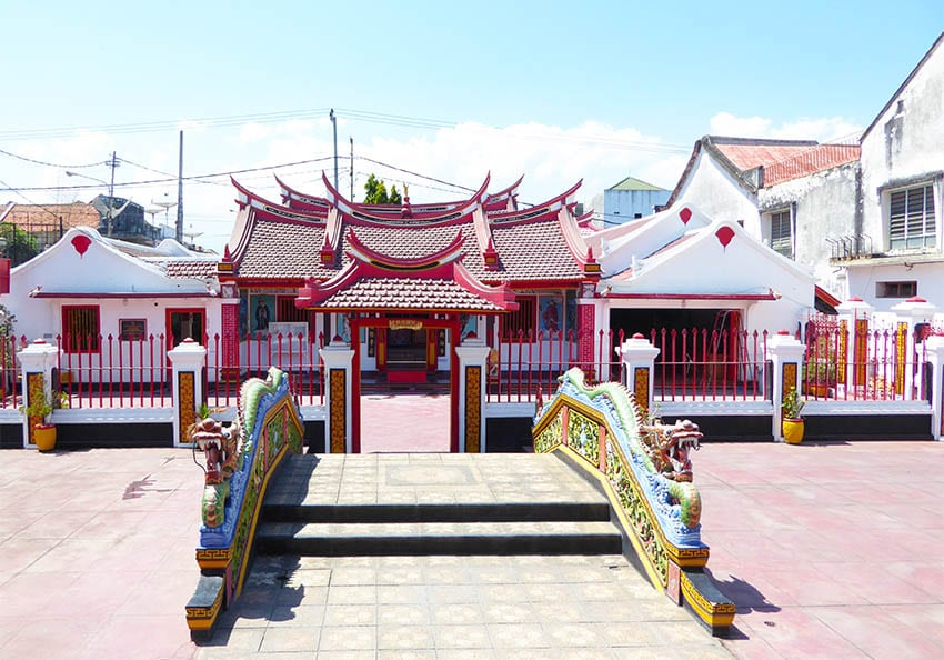 Chinese Buddhist Temple in Singaraja, Bali with brightly coloured carved dragons on the sides of the bridge leading to the red and white painted temple