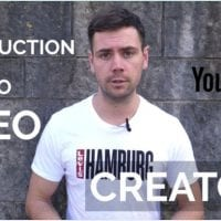 Greg Snell standing in front of a grey brick wall with the words Introduction to YouTube for Video Creators around him