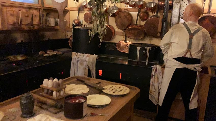 Old fashioned kitchen on the SS Great Britain, with copper pans hanging on the walls. Eggs on the counter and pies being made. The cook has an apron around his waist and is wearing braces.