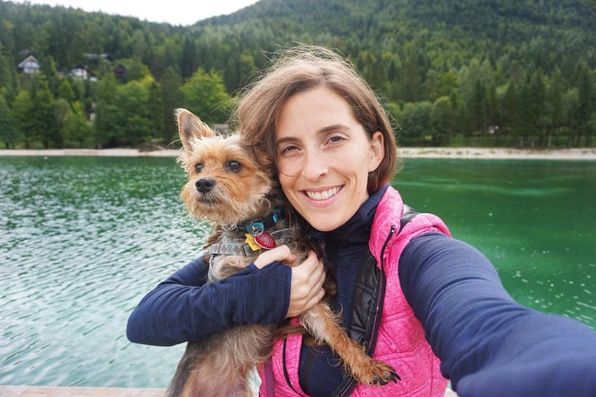 Woman wearing a blue top and pink padded gilest holding a small Yorkshire terrier with a lake and pine forest in the background