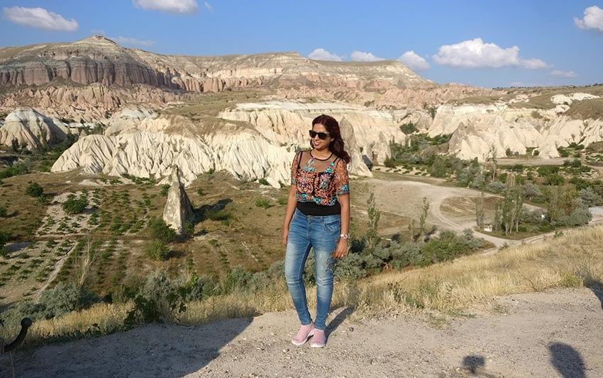 Woman wearing jeans and sunglasses in front of hills