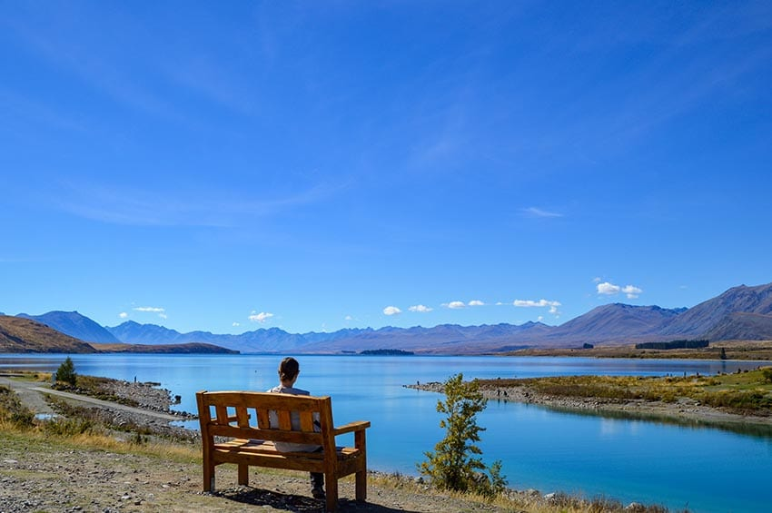 Woman sitting on a wooden bench looking out over a blue lake with mountains in the background and clear blue sky above.