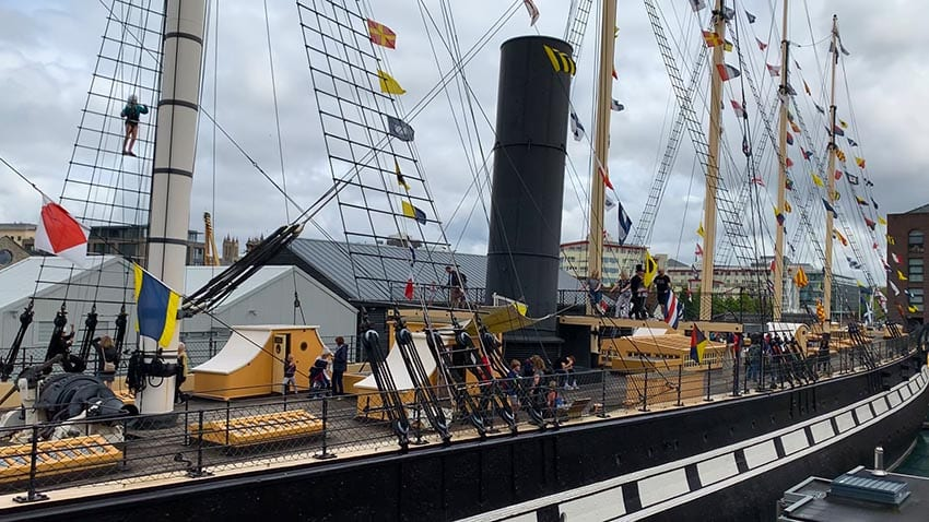 The Upper Deck of the SS Great Britain with black and cream sides tall black funnel and rigging with nautical flags. A person is climbing the rigging and the skies are grey.