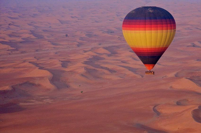 Hot air balloon with bands of purple, pink red orange and yellow and basket beneath flying over red sand dunes in the desert