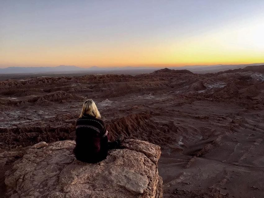 Leanne from The Globetrotter GP sitting with her back to us on a rock looking over the Atacama Desert in Chile as the sun sets in the distance.