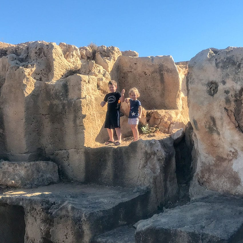 two young children standing on ruins at the Tombs of the Kings in Cyprus