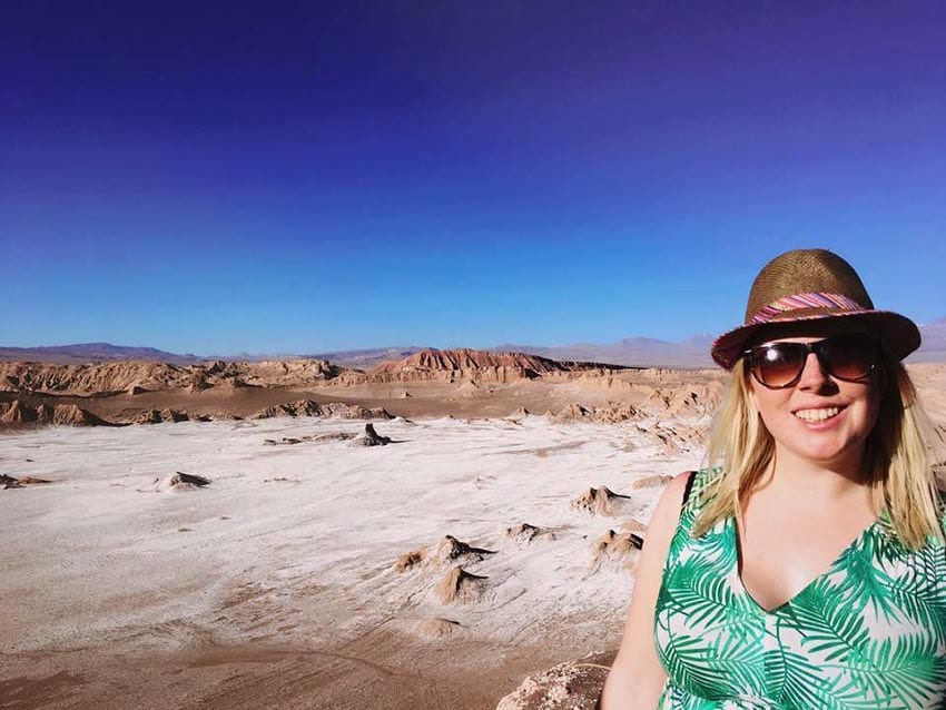 Leanne wearing a green v-neck dress, sunglasses and hat in the desert with hills behind and blue sky