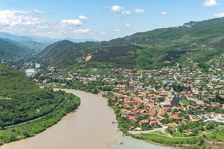 Mtskheta in Georgia - a long winding river with a town on the right hand side and green hills beyond