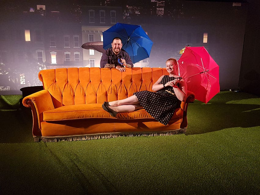 Roma in a black dress holding a red umbrella reclining on an orange sofa with her husband Russell behind the sofa holding a blue umbrella on the set at FriendsFest in London