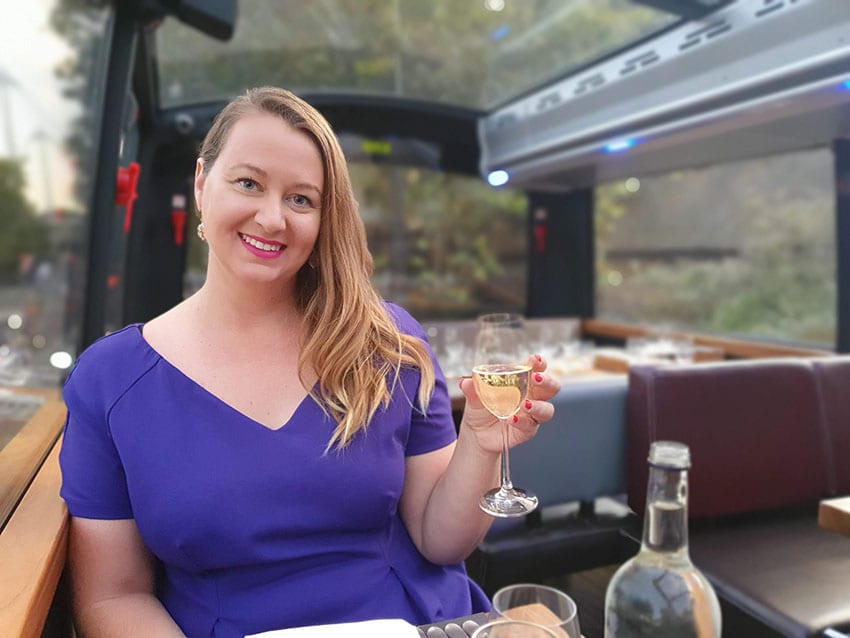 Roma in purple dress holding a glass of wine on the top deck of the Bustronome fine dining/bus tour around London