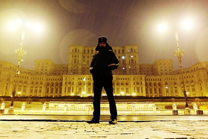 Steve standing in front of the Bucharest Palace of the Parliament wearing a dark jacket with the hood up and his hands in his pockets. It is night and it is raining