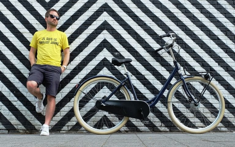 "Steve wearing a yellow t-shirt which says ""Je suis le maillot jaune"" (translation: I am the yellow jersey) standing with his back against a wall with black and white diagonal stripes next to a bicycle in Rotterdam"
