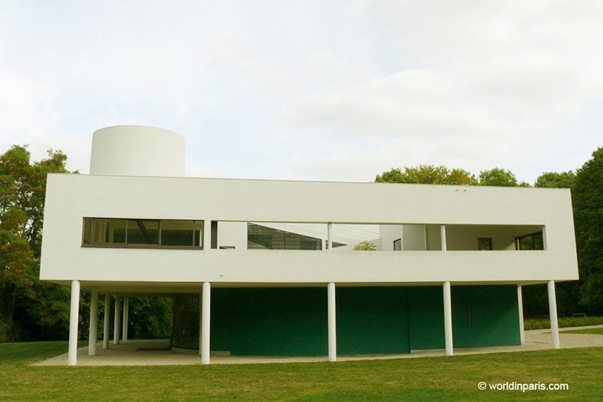 Villa Savoye a modern looking building with white rectangular box with rectangular windows supported on 5 thing columns with a round white tower in the left hand background.