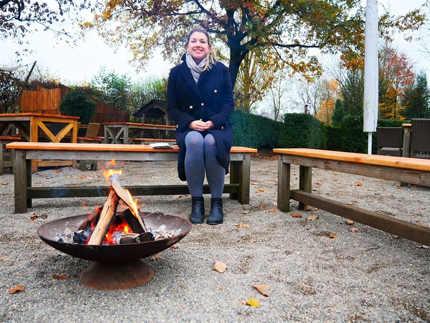 A smiling blonde lady wearing a navy coat with grey scarf and tights sitting on a bench warming herself in front of an open fire in a metal firepit at Archeon open air museum in the Netherlands