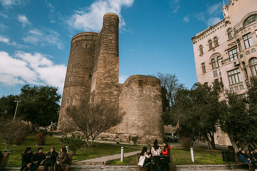 The Maiden Tower in Baku with trees round it and people in the foreground.