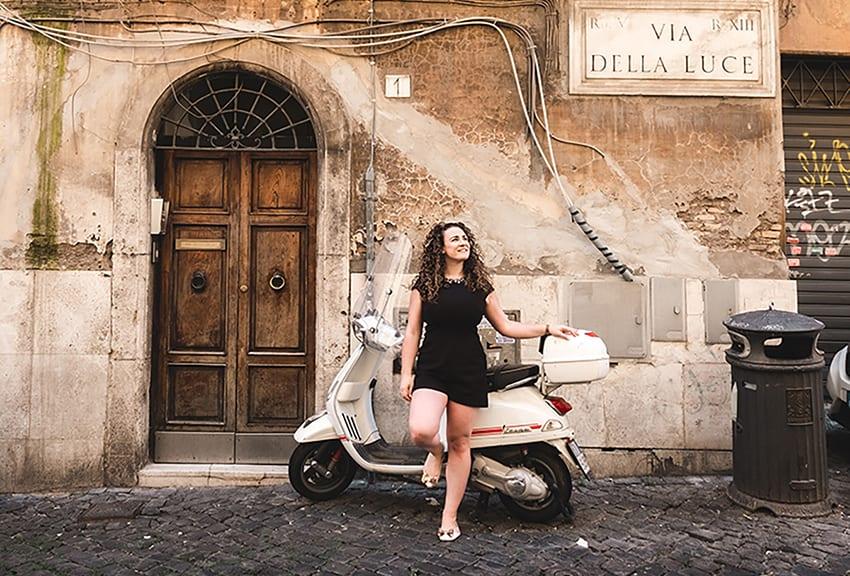 Michele in black dress leaning against a moped in an Italian street