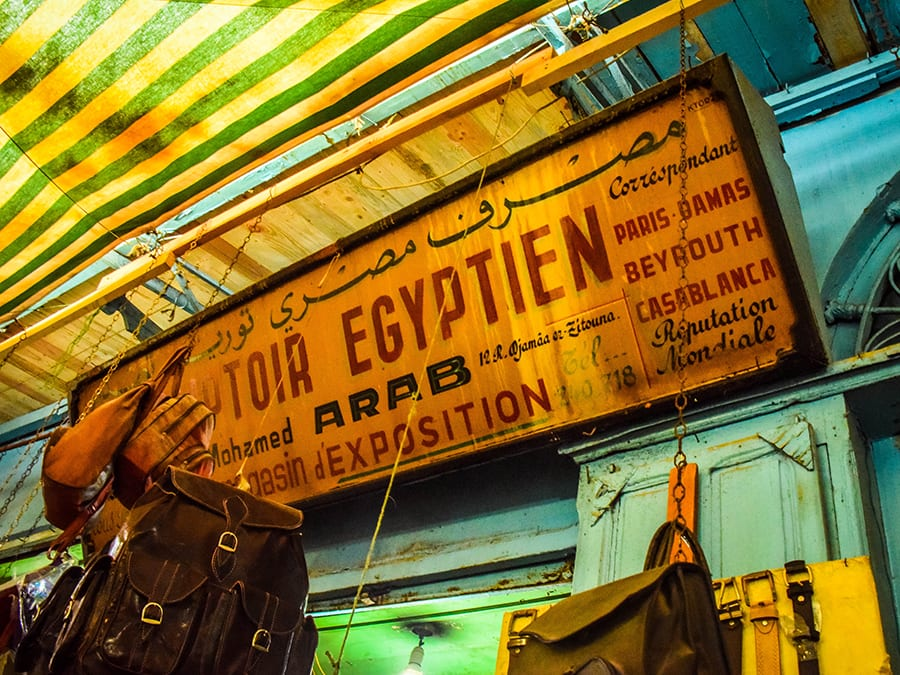 yellow and green striped awning over turquoise and green shuttering with brown leather backpack hanging from the roof and an old metal sign  with Egyptien exposition on it