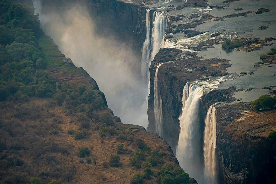 Victoria Falls - waterfalls with spray coming up between the two sides of land