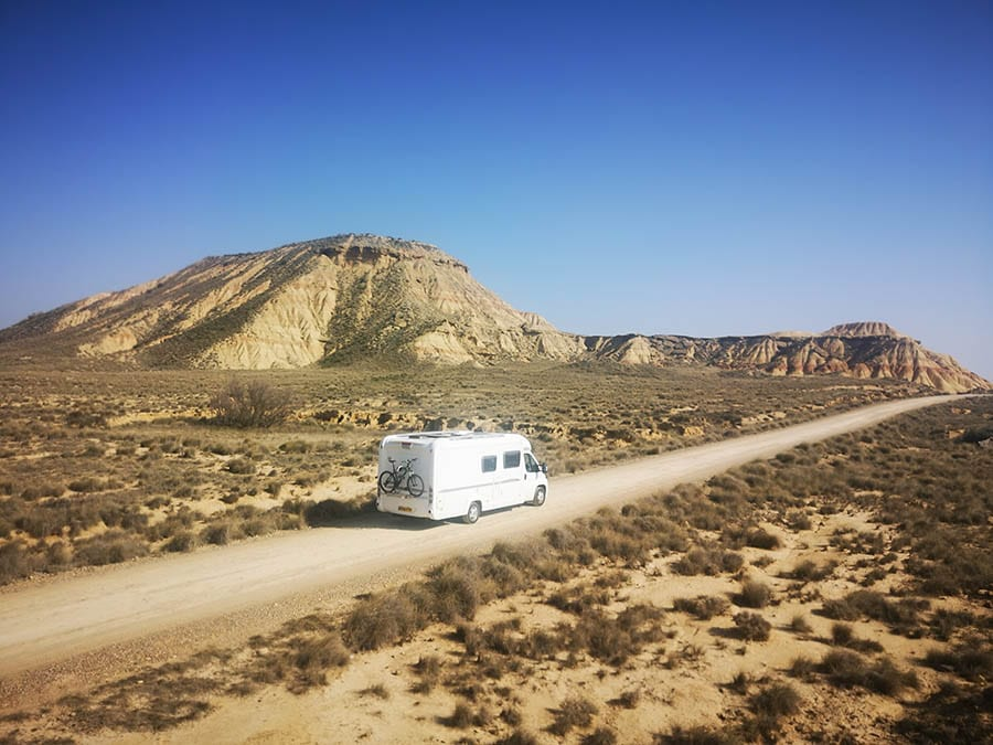 Destination Addicts' white campervan with bike on the back travelling through the Bardenas Reales in Northern Spain. There are sand coloured hills in the background and scrub bushes either side of the road.