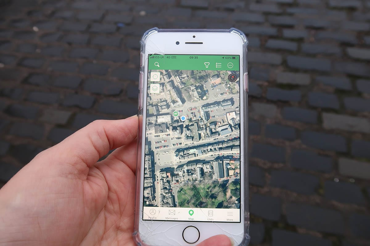 Geocaching map shown on an iPhone with a blue dot showing the position of the phone and a green symbol showing where the traditional geocache is