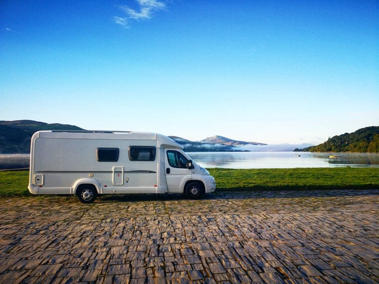 white camper van sitting on gravel with lake, blue skies behind