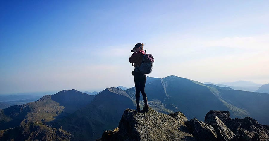 Woman standing on top of a mountain with a backpack on her back taking a photo of the mountains in the background