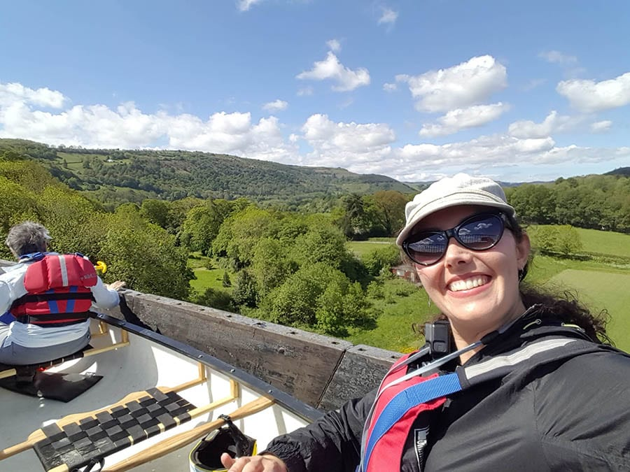 Girl wearing white hat and sunglasses smiling at the camera as she travels in a white boat along the Pontcysyllte Aqueduct with green trees and fields below.