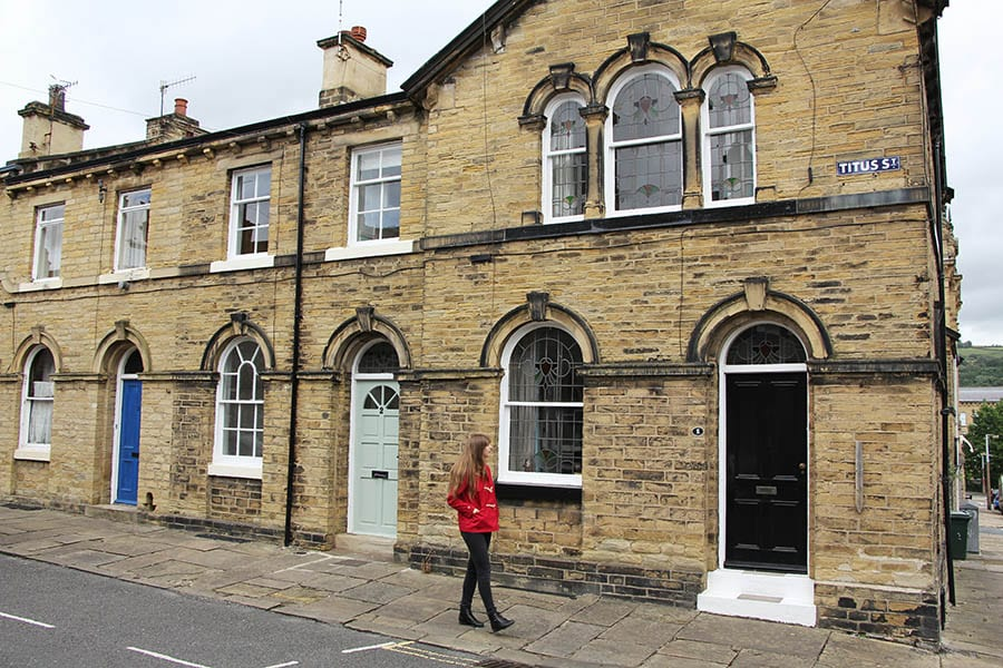 Girl with long brown hair wearing a red coat, black trousers and boots walking down a street called Titus St.