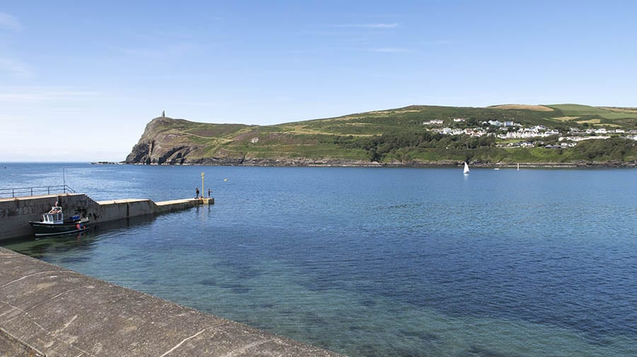 View of a bay with turquoise and blue sea with a pier. In the background are green hills in The Isle of Man UNESCO World Biosphere Region