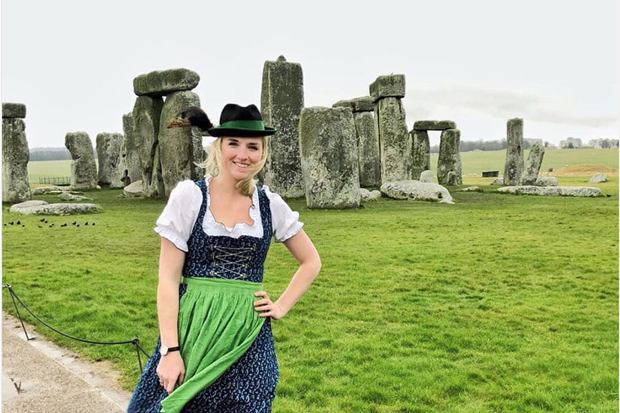 blonde lady in traditional Austrian Tyroll dress of white shirt with puff sleeve, under a blue sleevesless dress with lacing on the bodice and green apron and black hat with green ribbon standing in front of Stonehenge.