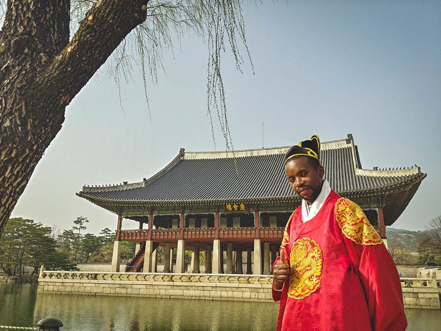 Roobens from Been Around the Globe, a black travel blogger in traditional Korean costume of red coat with gcol dragon symbol on front and sleeves, white collar and black and gold hat, giving the thumbs up in front of a pavilion surrounded by water