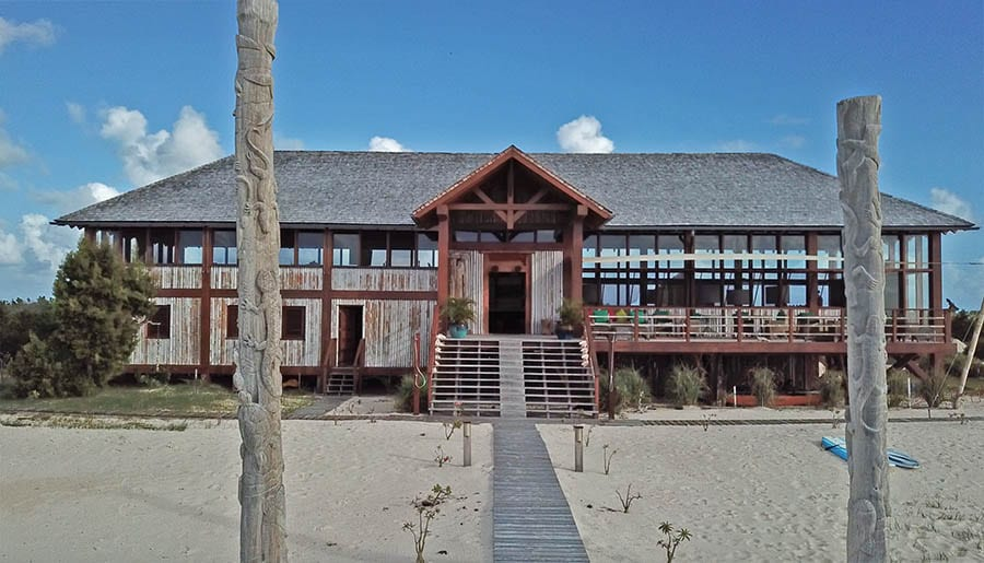 Wooden building with steps going up to it and long, tall glass windows. Two wooden poles with carvings of lizards are either side of the wooden walkway. Barbuda Belle Resort