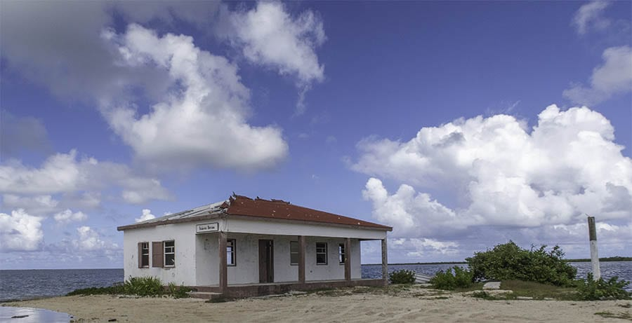 Derelict building in Barbuda with red roof and white walls