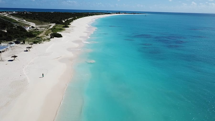 Long white sandy beach on the island of Barbuda with turquoise sea on the right and green land to the left