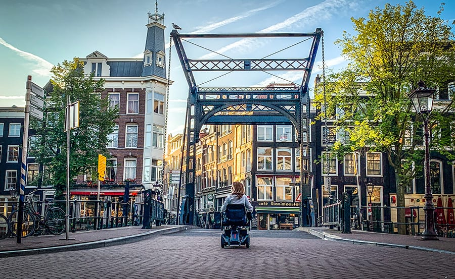 Sylvia from Spin the Globe in her wheelchair going across a paved road and under a metal bridge. There are trees wither side and buildings in the background. The windows are reflecting the buildings opposite and the sunny sky