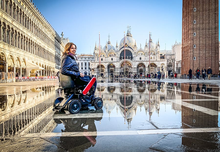 Sylvia from Spin the Globe in her wheelchair in blue coat in St Marks Square in Venice with the buildings reflecting in the puddles. The sun is shining and St Marks is in the background
