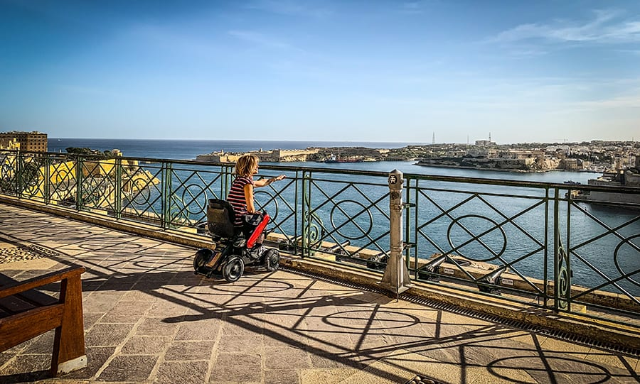 lady in a wheelchair looking through metal balustrades looting out over the sea in Valetta, Malta