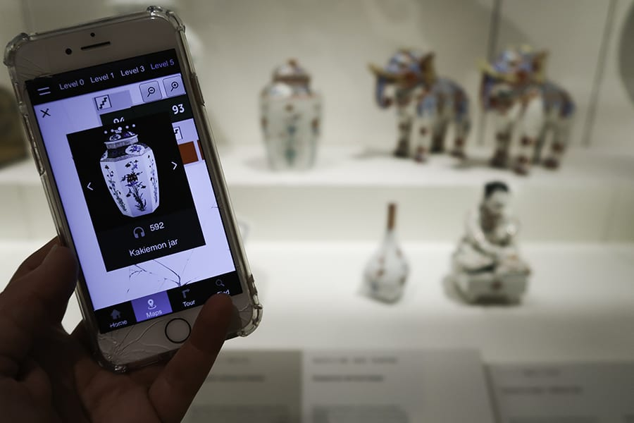 Mobile phone screen showing a vase with actual pottery vase, elephants and figurines in the background