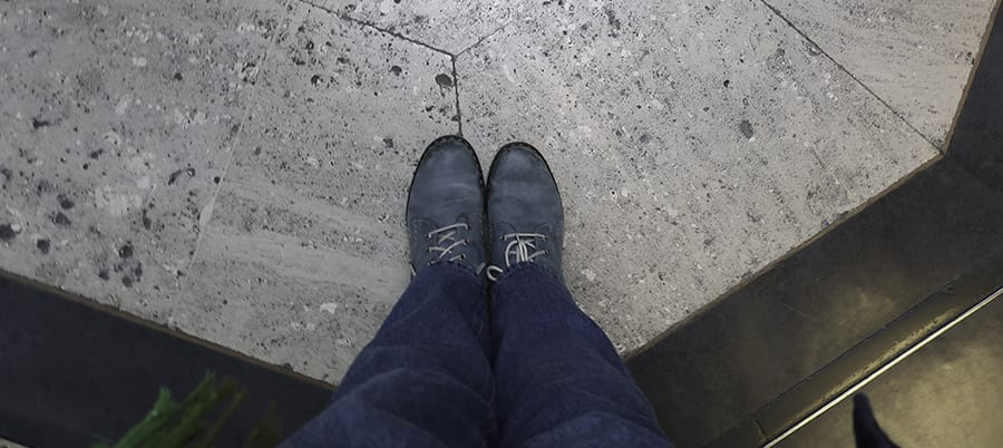 shot looking down on a pair of blue lace-up boots and jeans standing on a stone floor