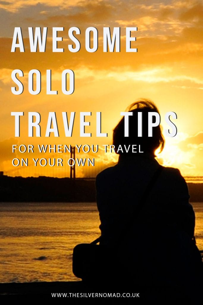 Silhouette of a woman looking out towards a suspension bridge and river as the sun goes down with the words Awesome Solo Travel Tips for when you travel on your own superimposed in white